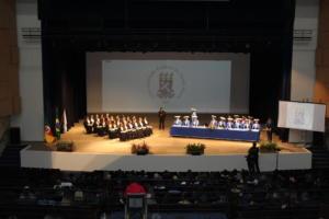 Imagem horizontal colorida vista de frente, à distância, de formandos em um palco
