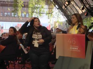 Mulher fazendo tradução para libras, movimentando aos mãos, ao lado de outra mulher, e o cartaz do 46 festival de cinema de gramado