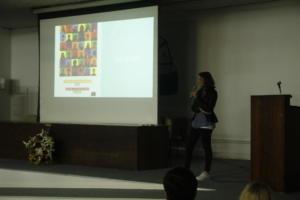 FOto horizontal colorida de mulher jovem em um palco próxima a um projetor