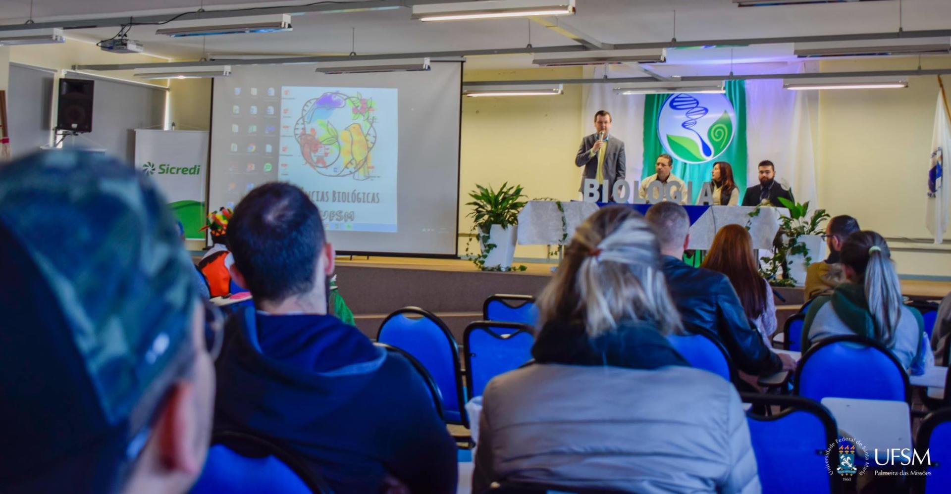 Imagem mostra um homem em pé, ao microfone, falando para pessoas em um auditório