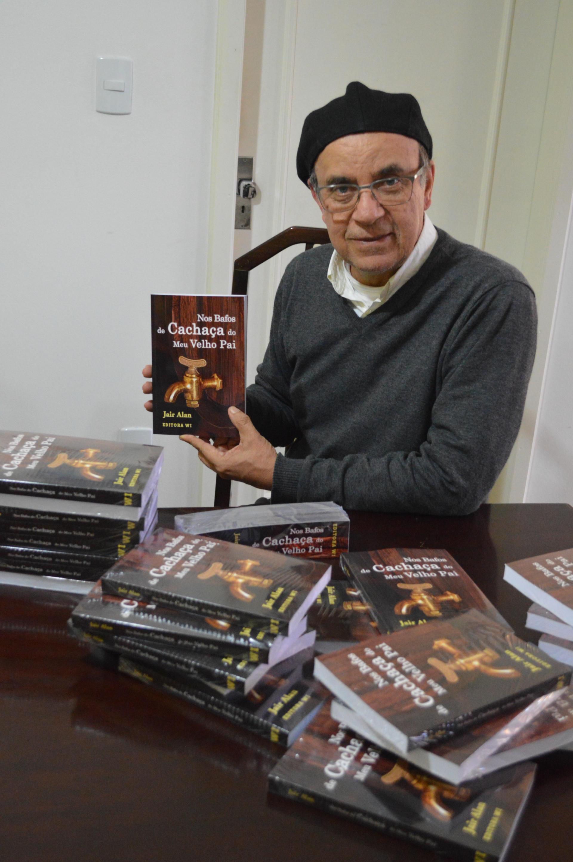 Foto colorida em pé mostra Jair Alan sentado com livros espalhados sobre a mesa