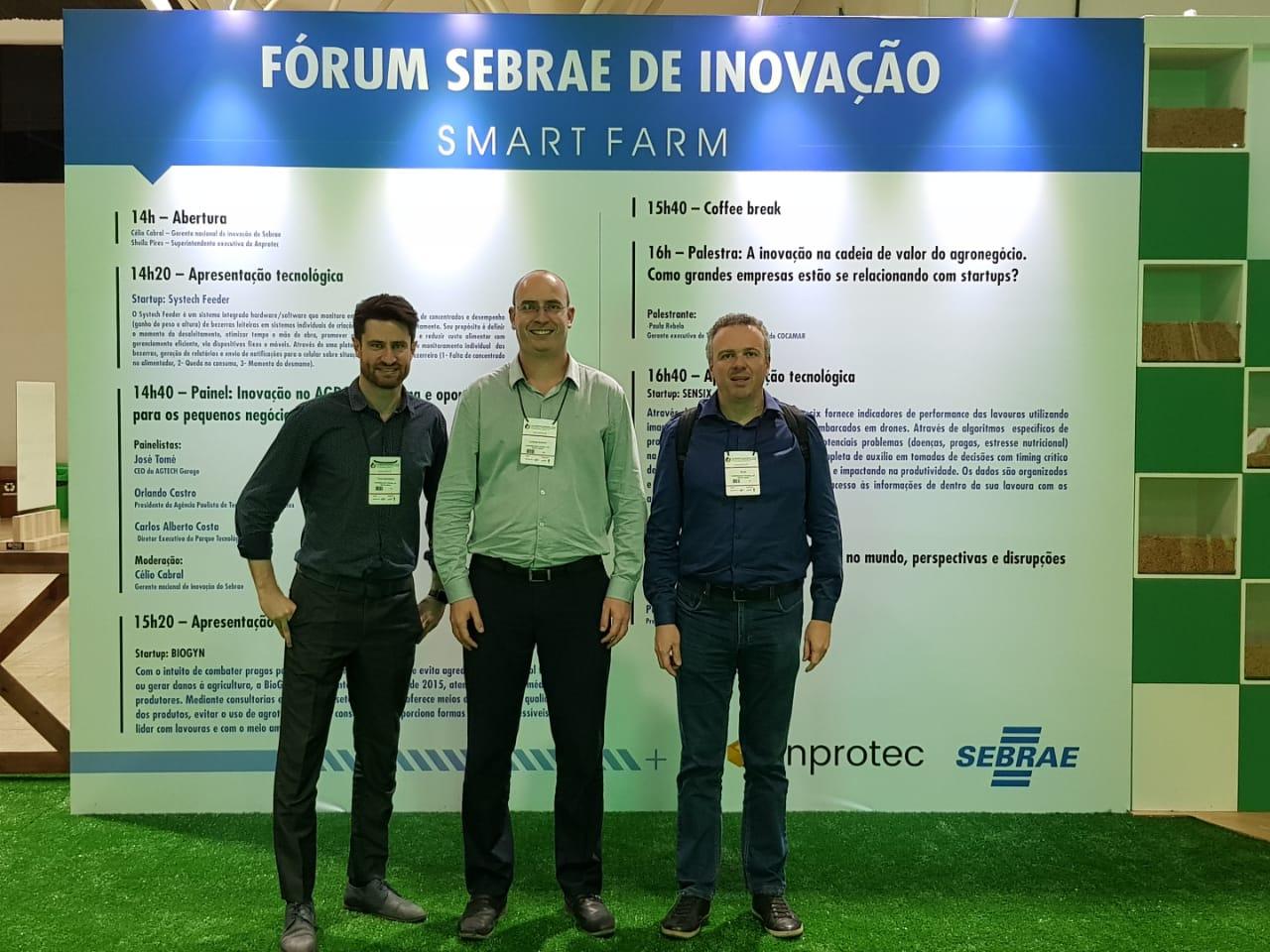 Foto horizontal colorida mostrando Tiago Marchezan, Luciano Schuch e Silon Procath em frente a um banner do Fórum Sebrae de Inovação