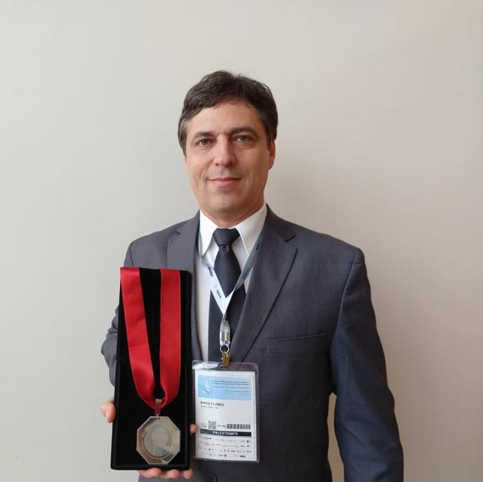 Foto de Érico Marlon de Moraes Flores mostrando a medalha recebida