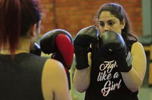 Foto com duas mulheres lutando box chinês. Uma delas está de costas e a outra de frente.