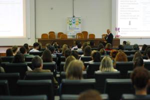 Foto do simpósio com perspectiva do final da sala, mostrando público sentado e palestrando à frente da mesa com projeção em slide à direita