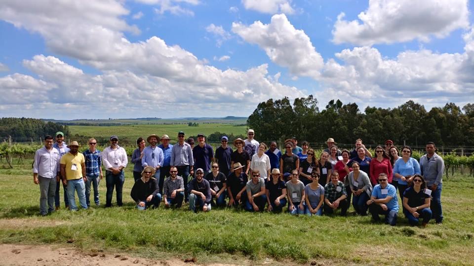 Foto colorida horizontal de um grande grupo de participantes posando, alguns em pé e outros agachados, para foto em uma área rural, com árvores ao fundo