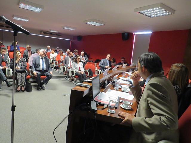 Foto em perspectiva da parte da mesa com os palestrantes e do público assistindo à palestra em um auditório pequeno com uma das paredes em vermelho. Um das pessoas na plateia é o reitor Burmann