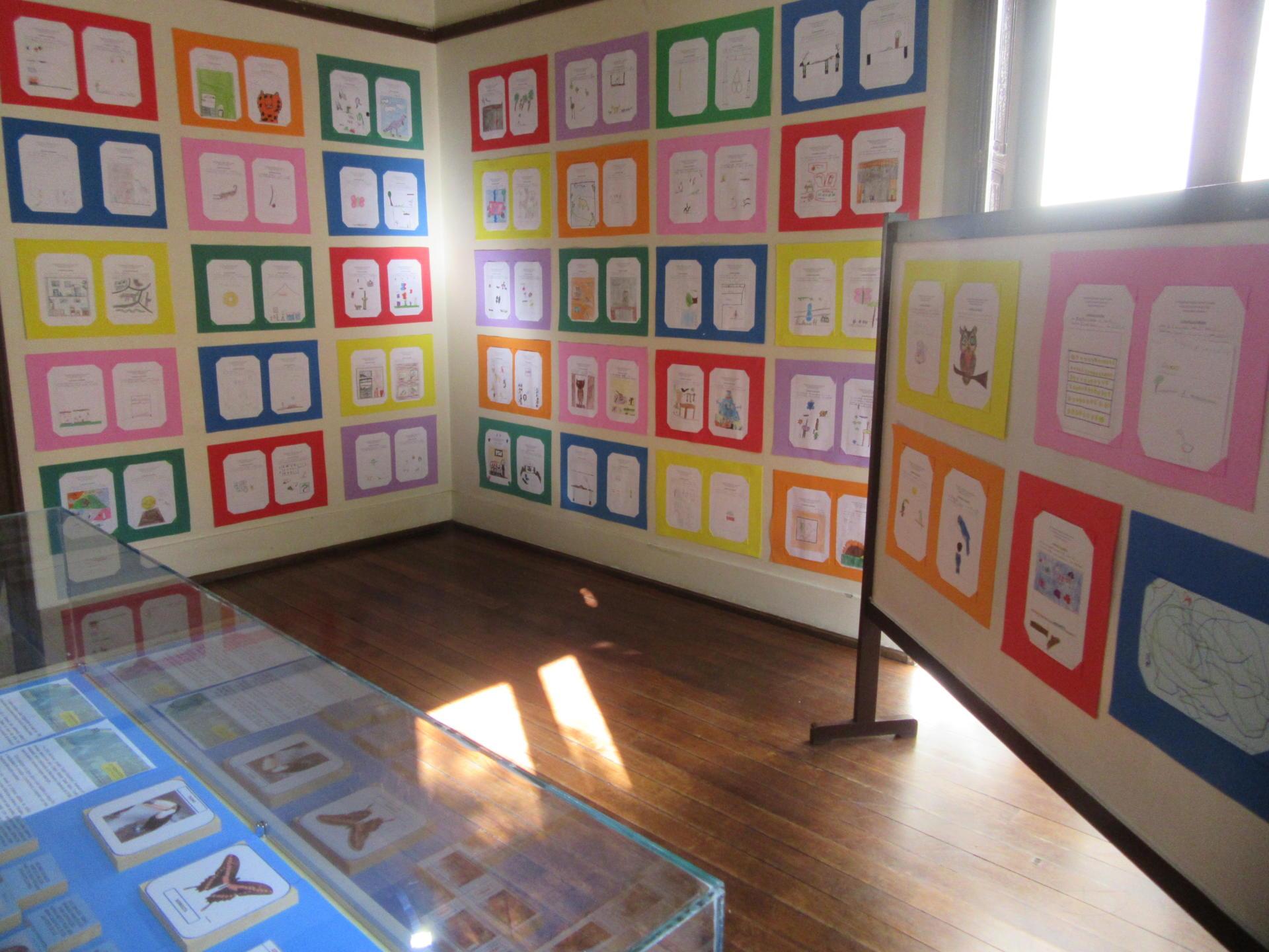 Foto horizontal em cores mostrando os desenhos feitos pelas crianças colados em cartazes coloridos fixados em painéis