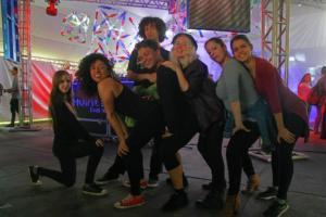 Sete pessoas fazem pose para a foto como se mostrassem uma coreografia de dança