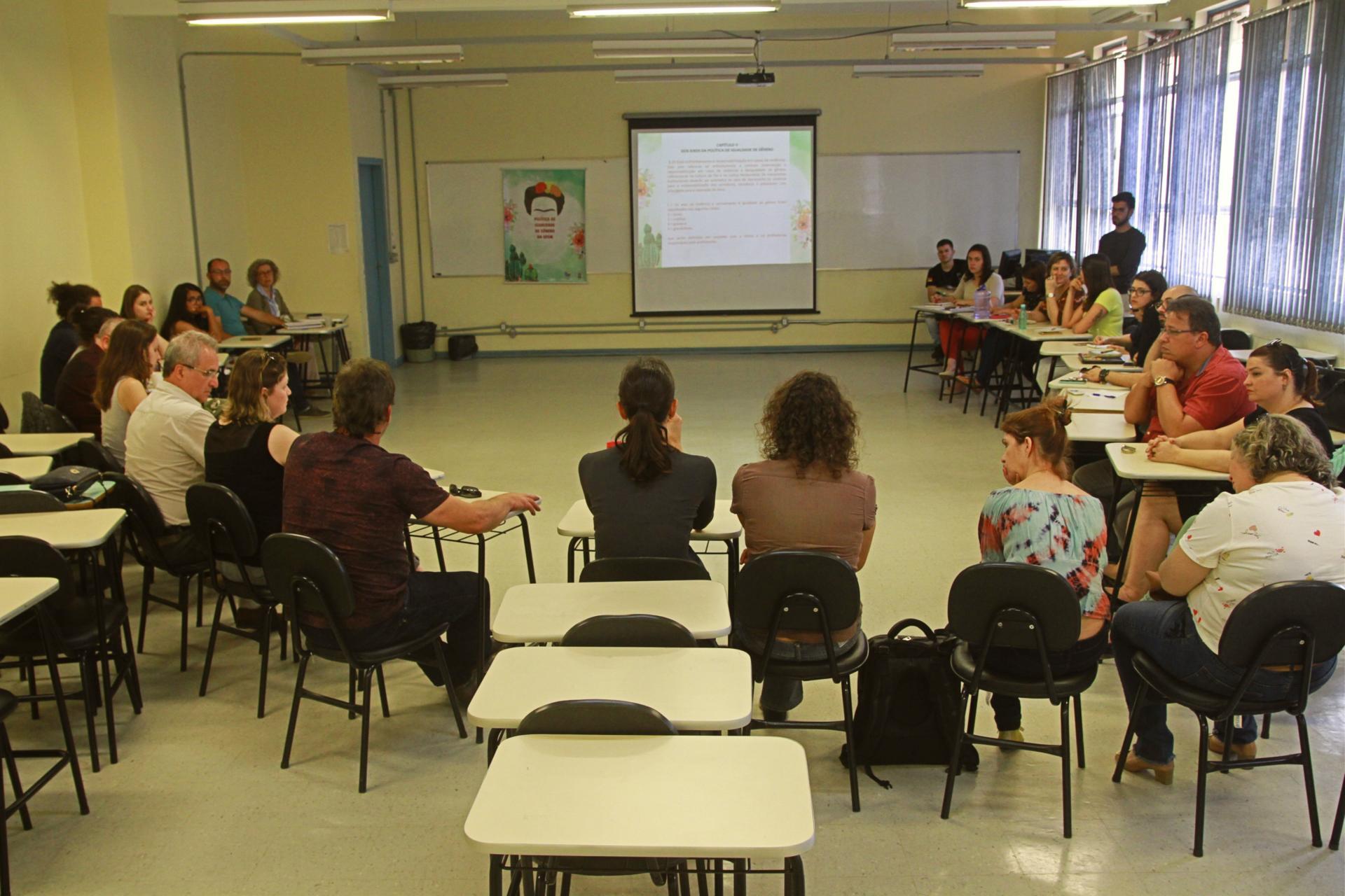Pessoas reunidas em uma sala de aula em semicírculo. À frente há um cartaz com a imagem da Frida Kahlo e uma projeção. A imagem da projeção está muito distante e não é possível identificar o que está escrito.