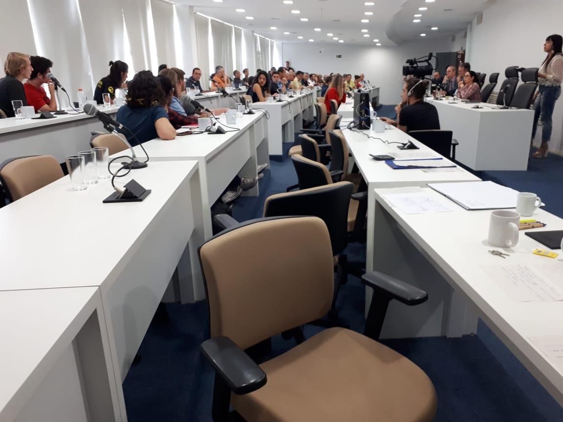 Sala dos conselhos, com várias mesas, as primeiras vazias e as seguintes ocupadas pelos conselheiros sentados. É possível perceber uma câmera de vídeo gravando os pronunciamentos