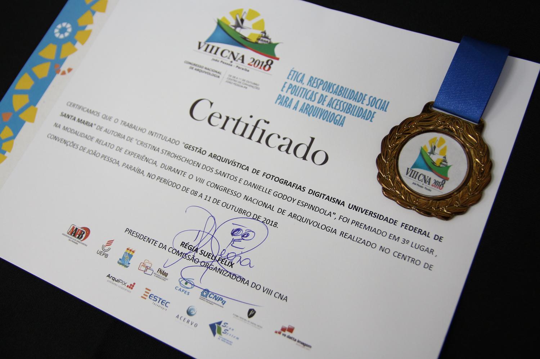 Foto em cores mostrando em primeiro plano o certificado de premiação do projeto