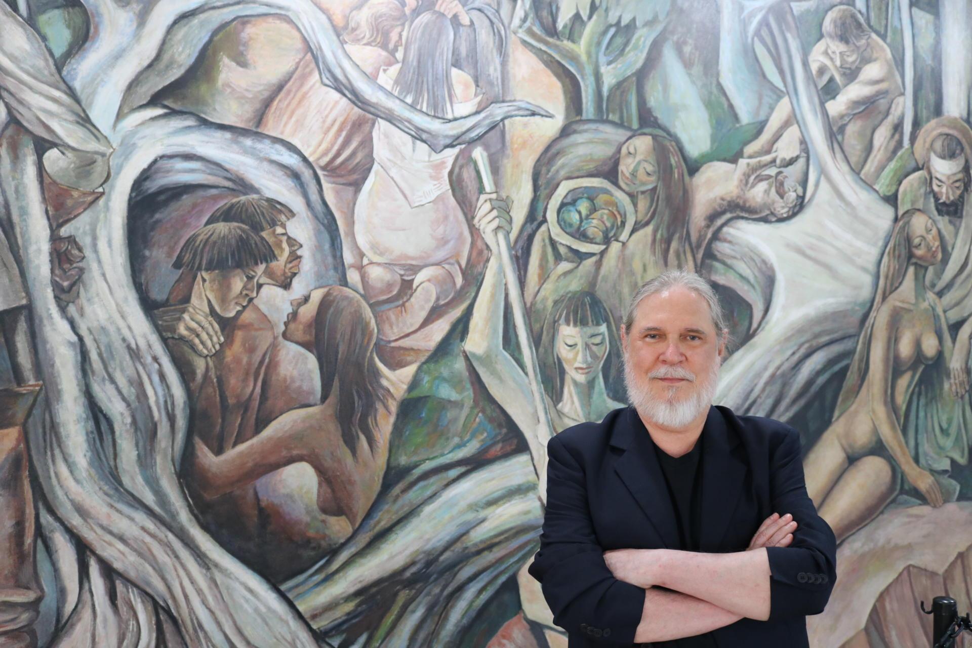 Artista posa em frente ao painel que restaurou, que traz representações de indígenas