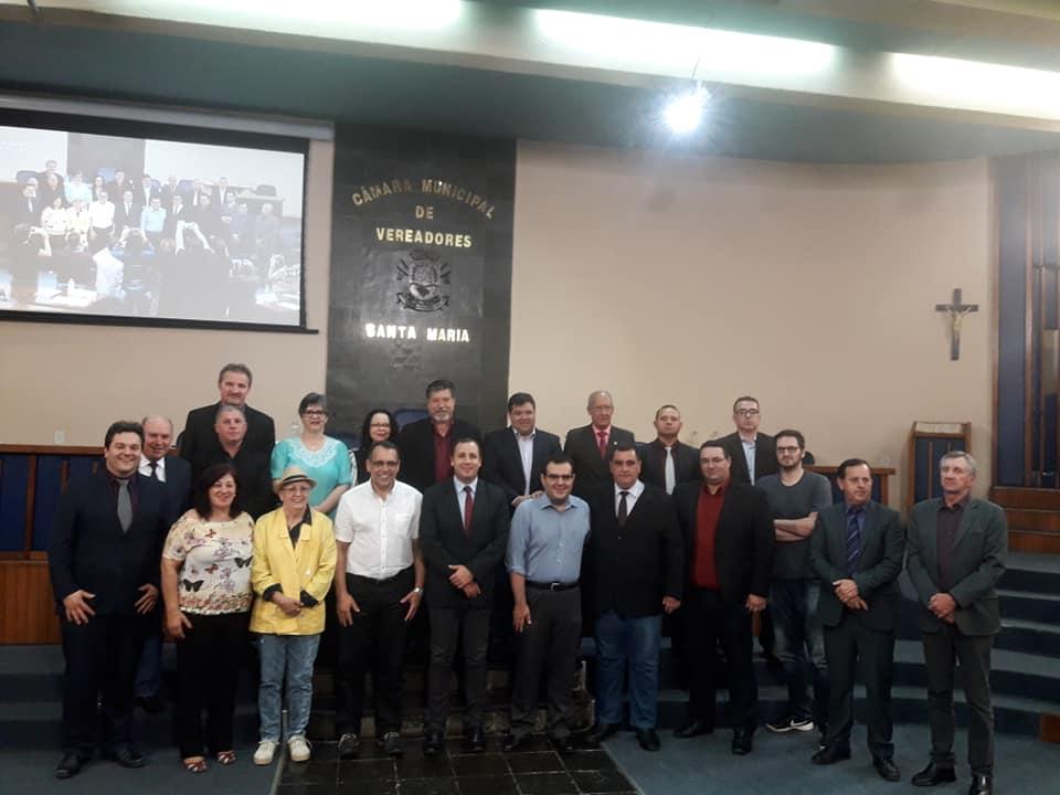 Foto colorida horizontal com os representantes da UFSM e os vereadores posando em frente ao plenário da Câmara