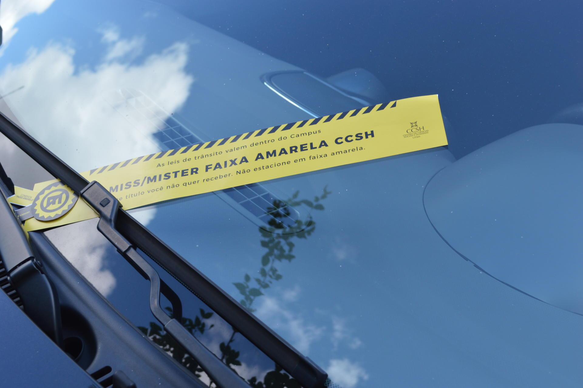 Foto de uma faixa da campanha, em amarelo, colocada sobre o parabrisa de um carro