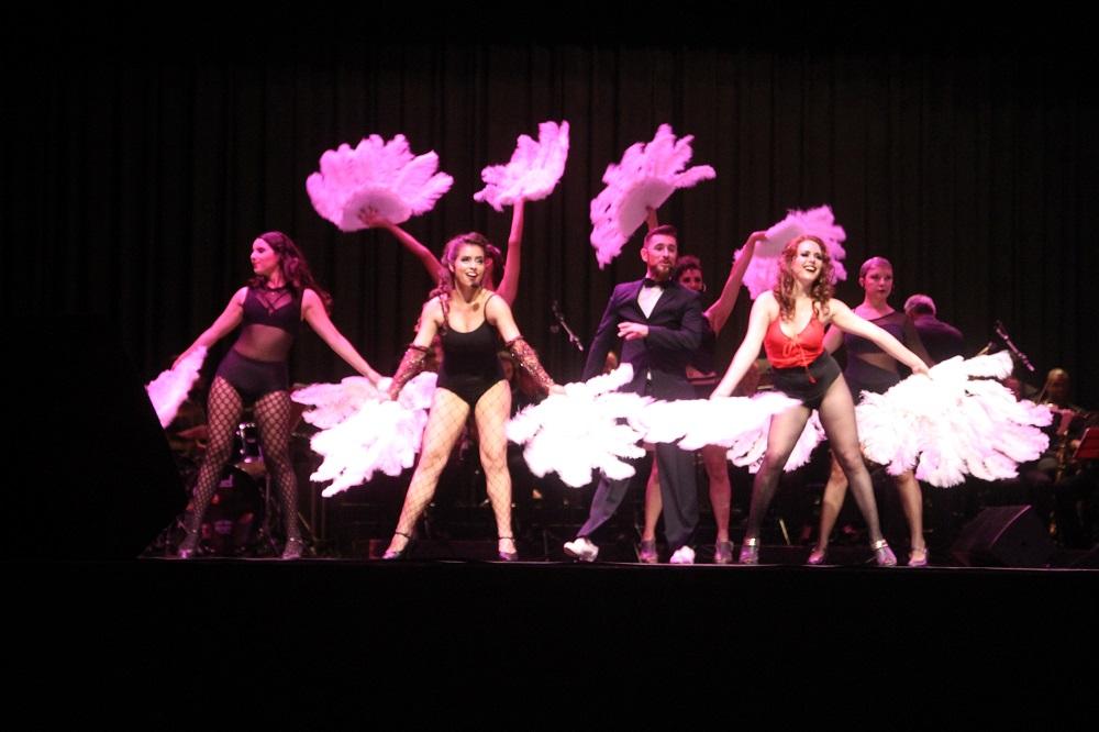 Mulheres dançam com plumas em suas mãos ao lado de um homem