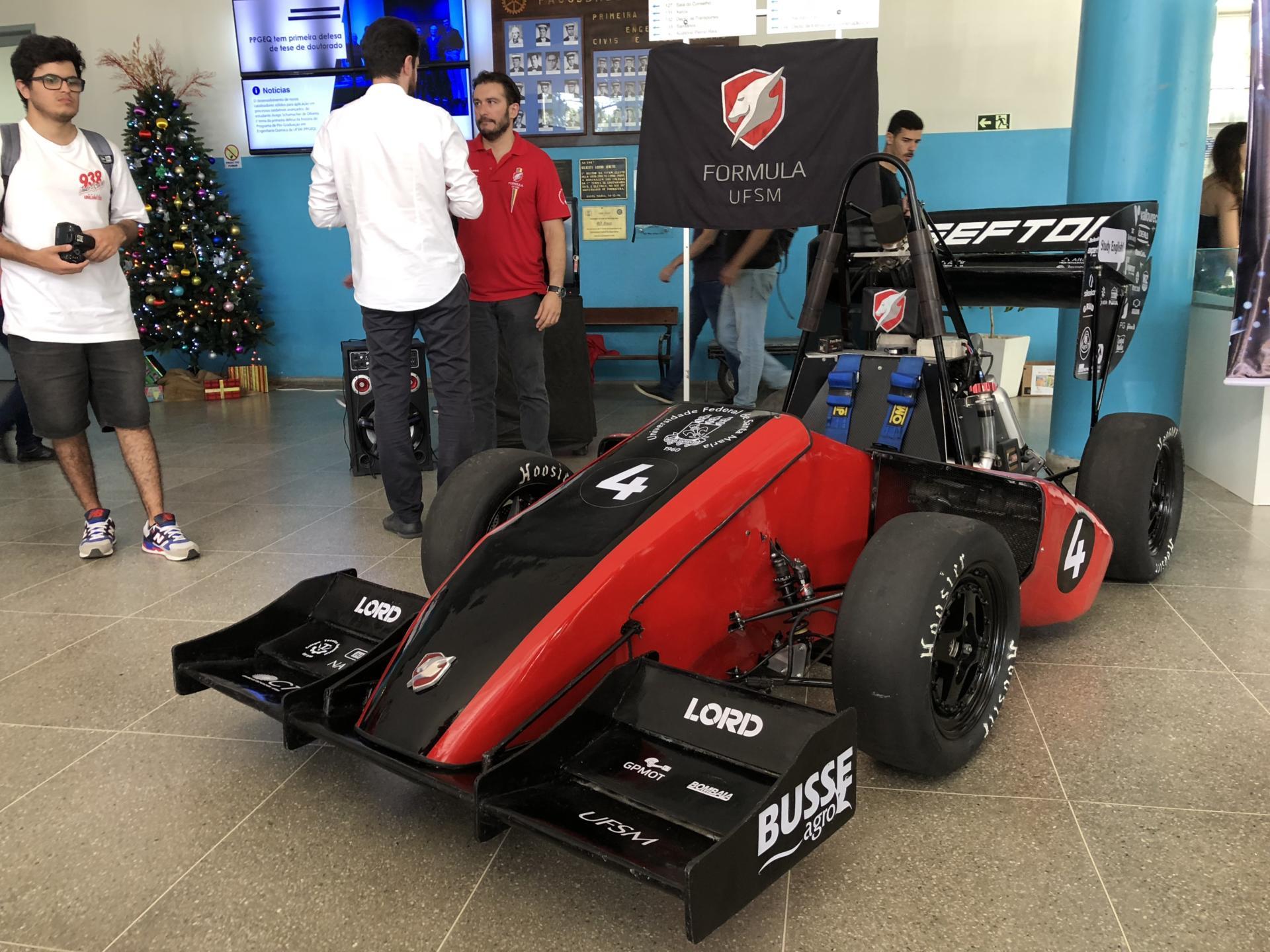 Pessoas contemplam o protótipo do carro, nas cores preto e vermelho, no hall do CT