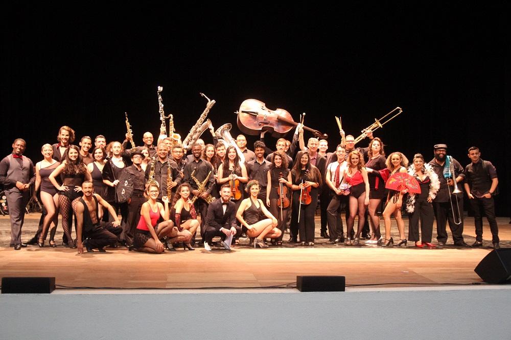 Várias pessoas no palco em pé e algumas sentadas. Algumas seguram instrumentos como violoncelo, violino e flauta