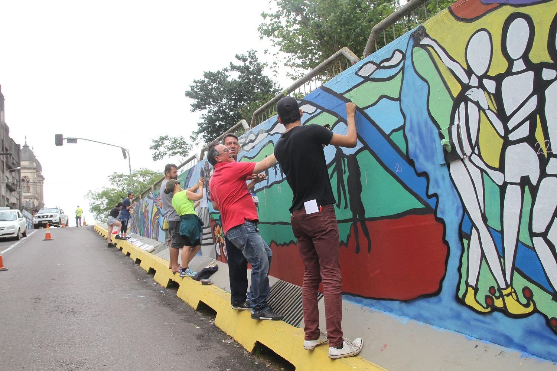 Pessoas pintam painel no muro que leva em direção ao viaduto Evandro Behr