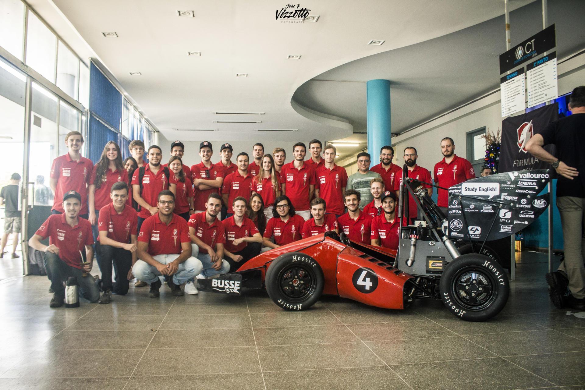 Em torno de 20 componentes da equipe Formula UFSM, de camiseta vermelha, posam junto ao protótipo do carro, no hall do CT