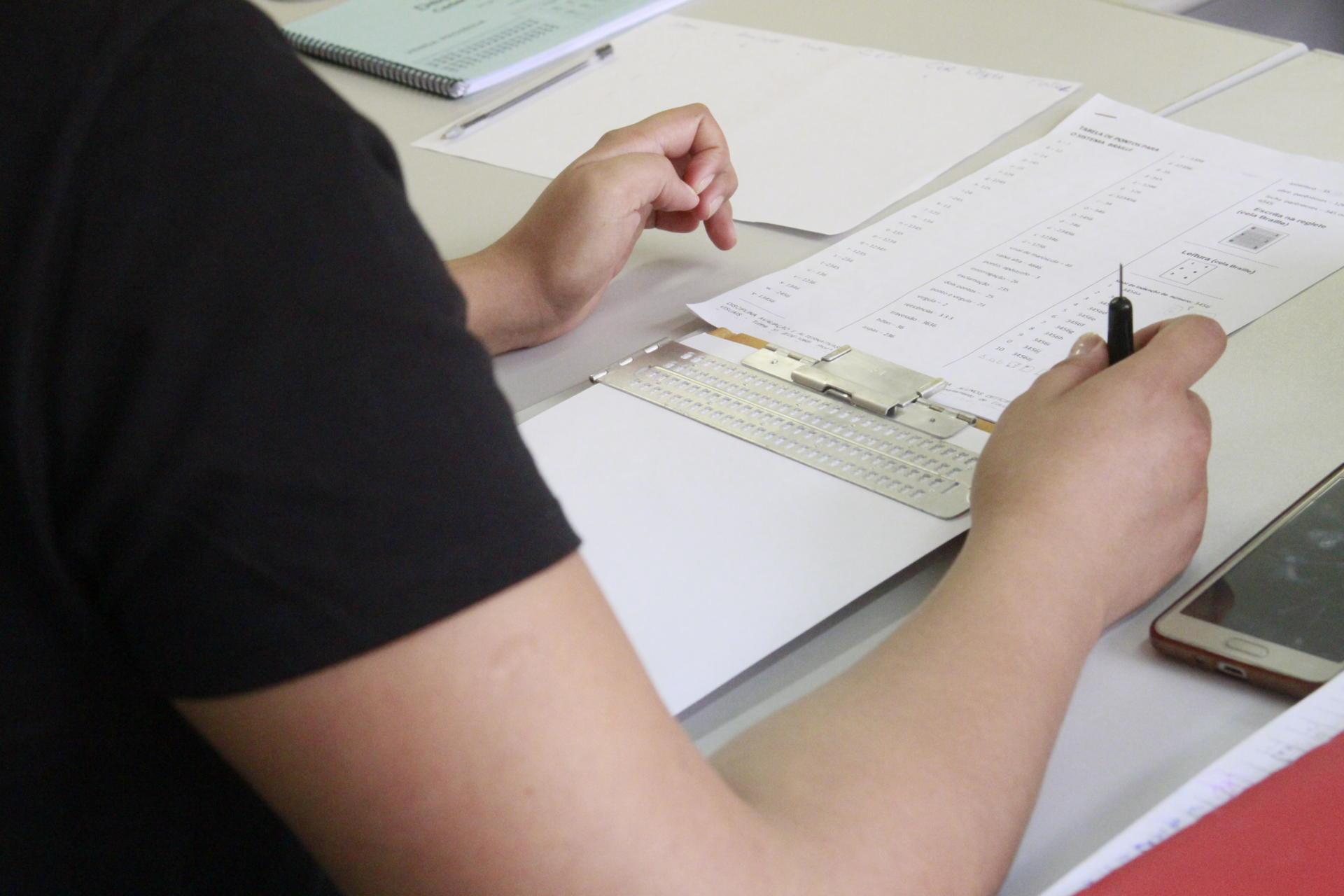 Foto colorida detalha participante em atividade prática de escrita em Braille