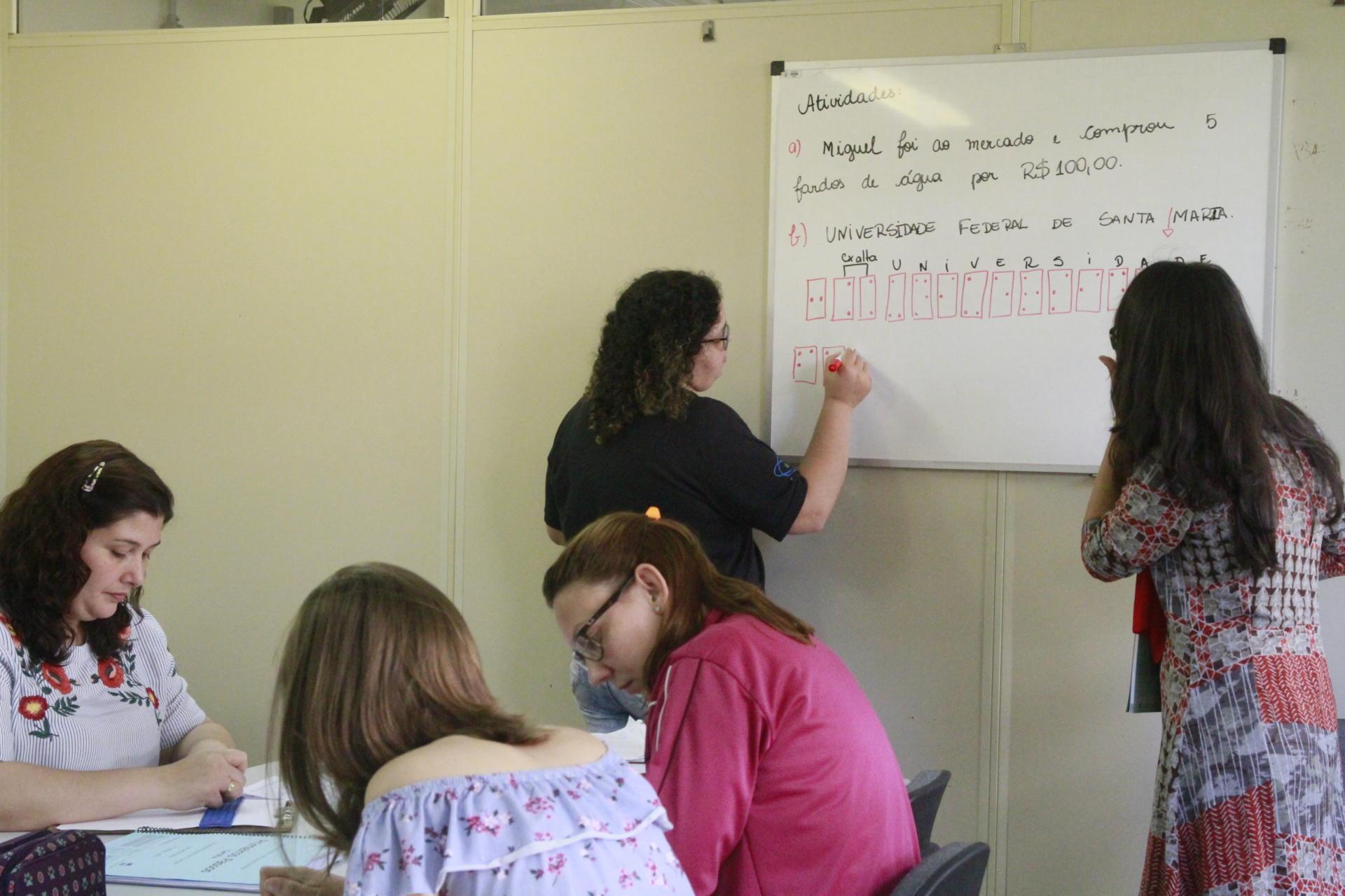 Foto colorida horizontal em que participantes do curso desenham símbolos de Braille em um quadro