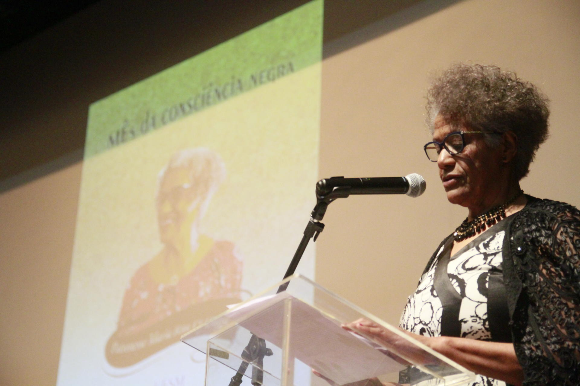 À direita, mulher no púlpito. Ao fundo, imagem projetada com a peça de divulgação do Mês da Consciência Negra