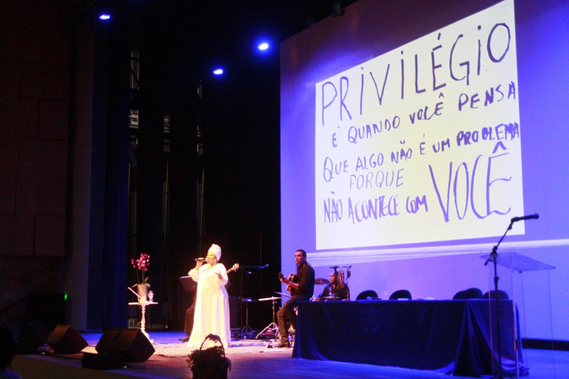 Mulher cantando e atrás, no telão, uma frase sobre privilégio