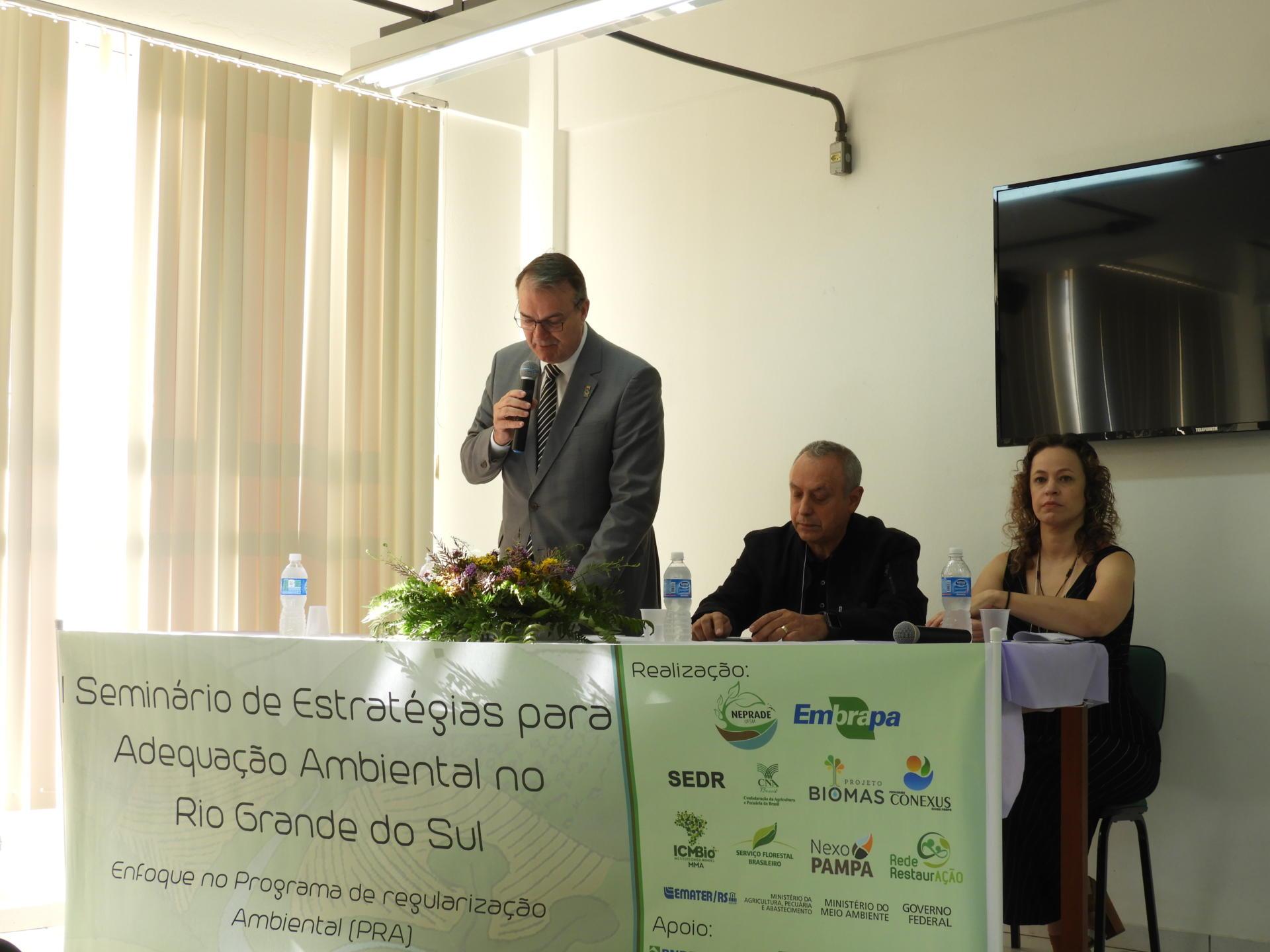 Foto horizontal colorida mostra o reitor, em pé, falando ao microfone, ao lado de outras duas pessoas sentadas à mesa oficial