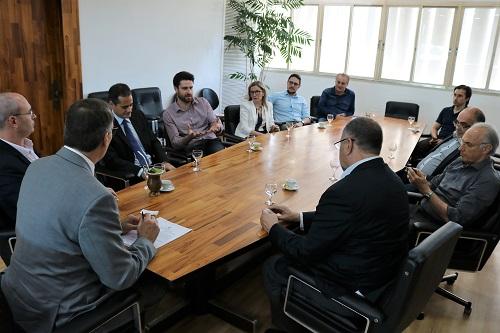 Mesa de reuniões com 11 pessoas, incluindo reitor e presidente da empresa