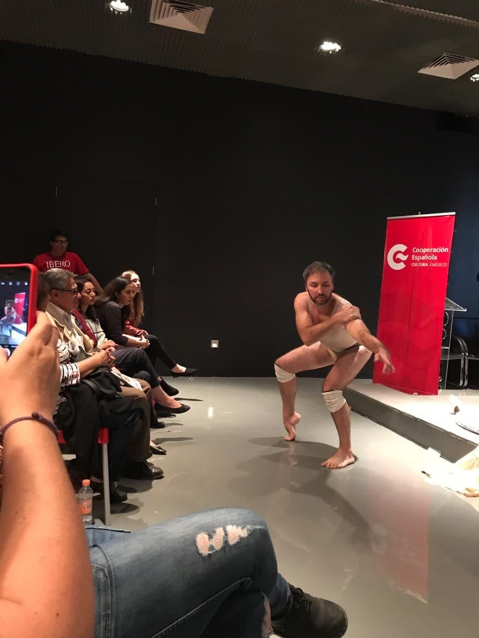 Foto vertical colorida mostrando o professor Berté durante sua performance em um espaço interno, próximo ao público que o assiste