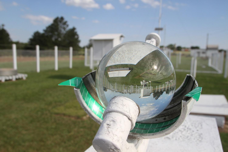 O elemento principal da foto é uma esfera de vidro que reflete a imagem invertida. Abaixo dela uma espécie de calota metálica curvada com uma marcador verde. O marcador traz uma escala em branco como uma régua