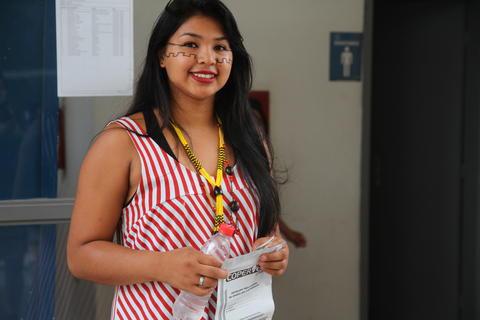 Jovem indígena segurando prova e uma garrafa de água. O rosto dela está pintado com um símbolo semelhante a uma torre nas maçãs do rosto