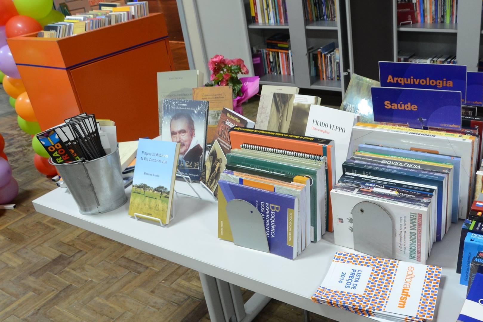 Foto colorida horizontal mostra, sobre uma mesa, itens da Livraria e da Editora que estarão à venda no evento