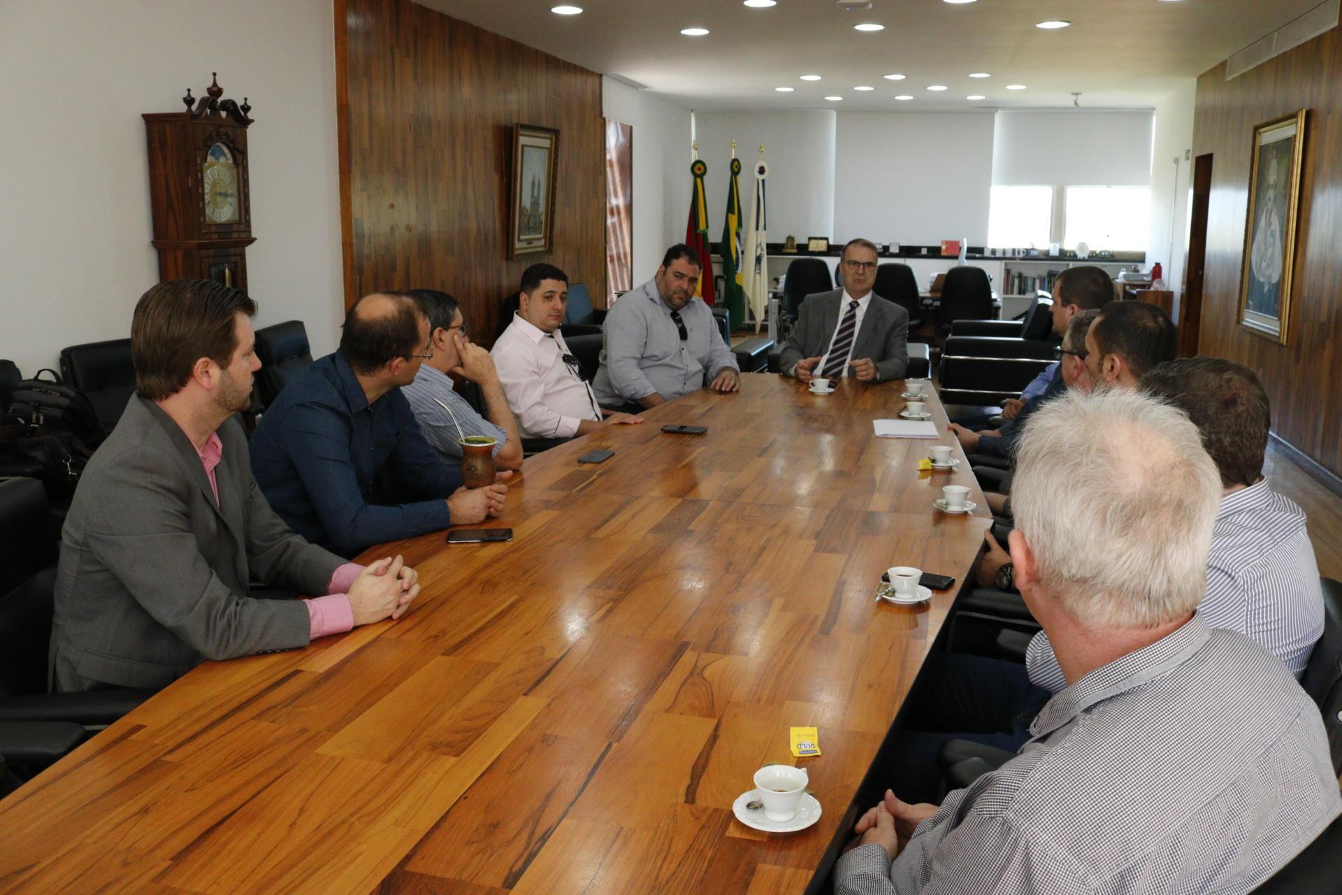 Vários homens sentados em uma mesa retangular conversam com o reitor, sentado na cabeceira