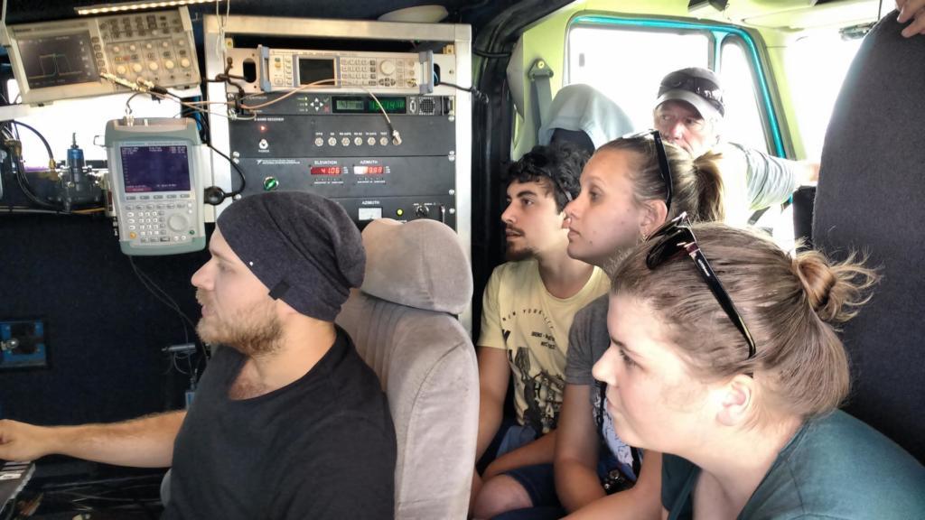 Grupo de pessoas observa telas em uma estação semelhante a uma van, cheia de aparelhos tecnológicos