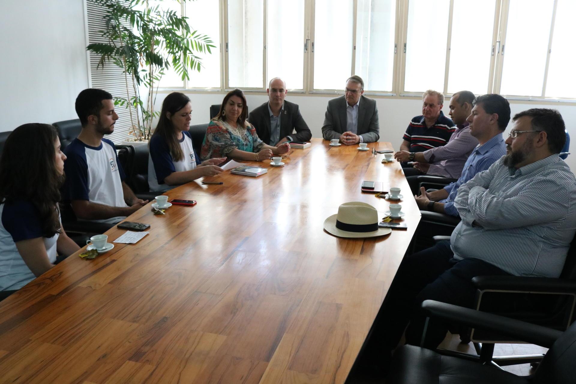 Em torno da mesa do reitor, estudantes, pró-reitores, vice-reitor e o reitor