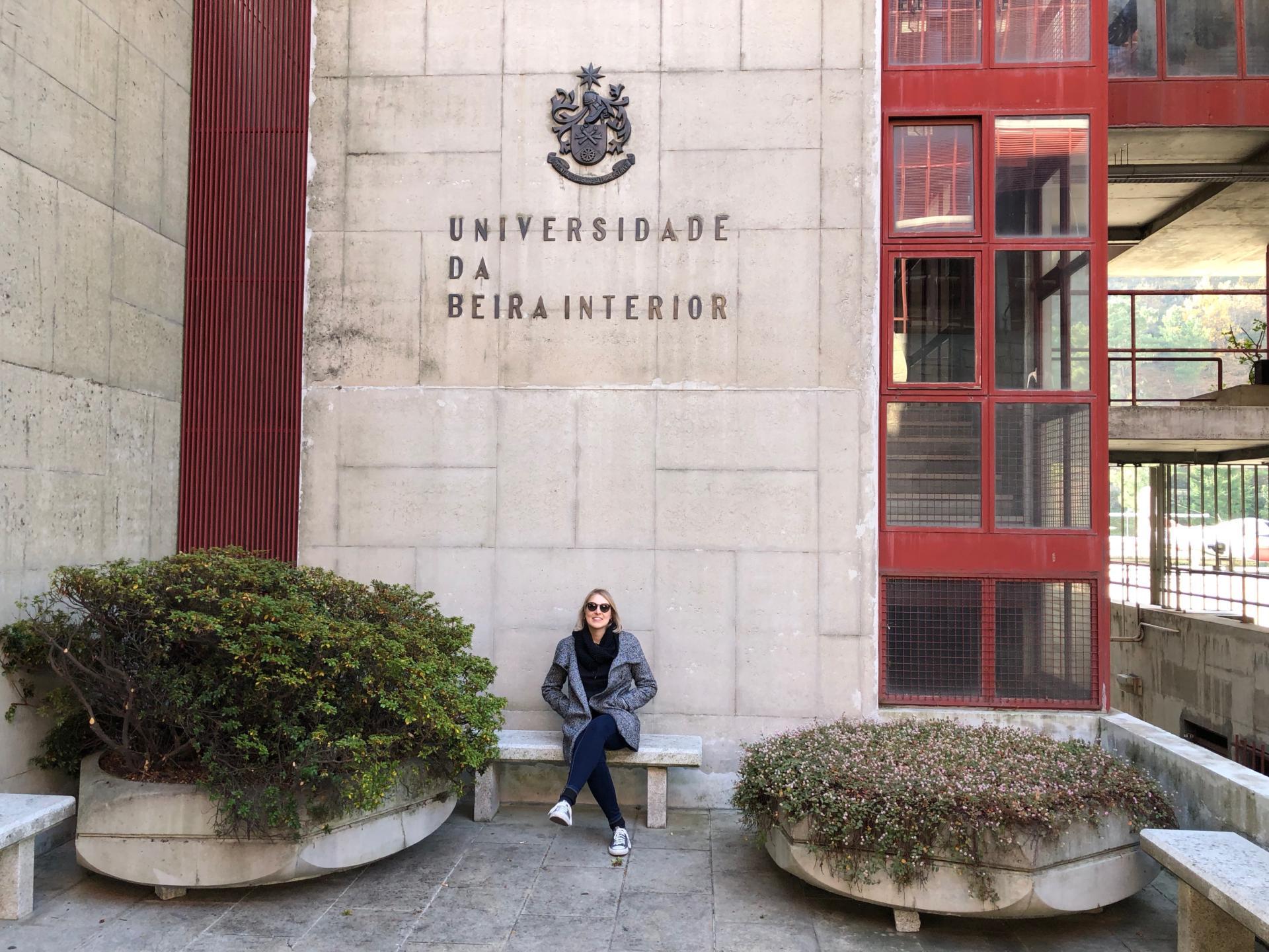 Foto colorida horizontal mostra Carolina sentada em um espaço externo da UBI, à frente de uma parede com o nome e o símbolo da Universidade, e dois grandes vasos de plantas ao lado
