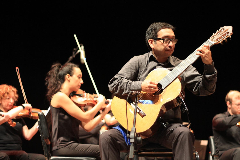 Em primeiro plano, músico toca violão. Em segundo plano, grupo de violinistas acompanham a música. Todos estão sentados no palco Centro de Convenções