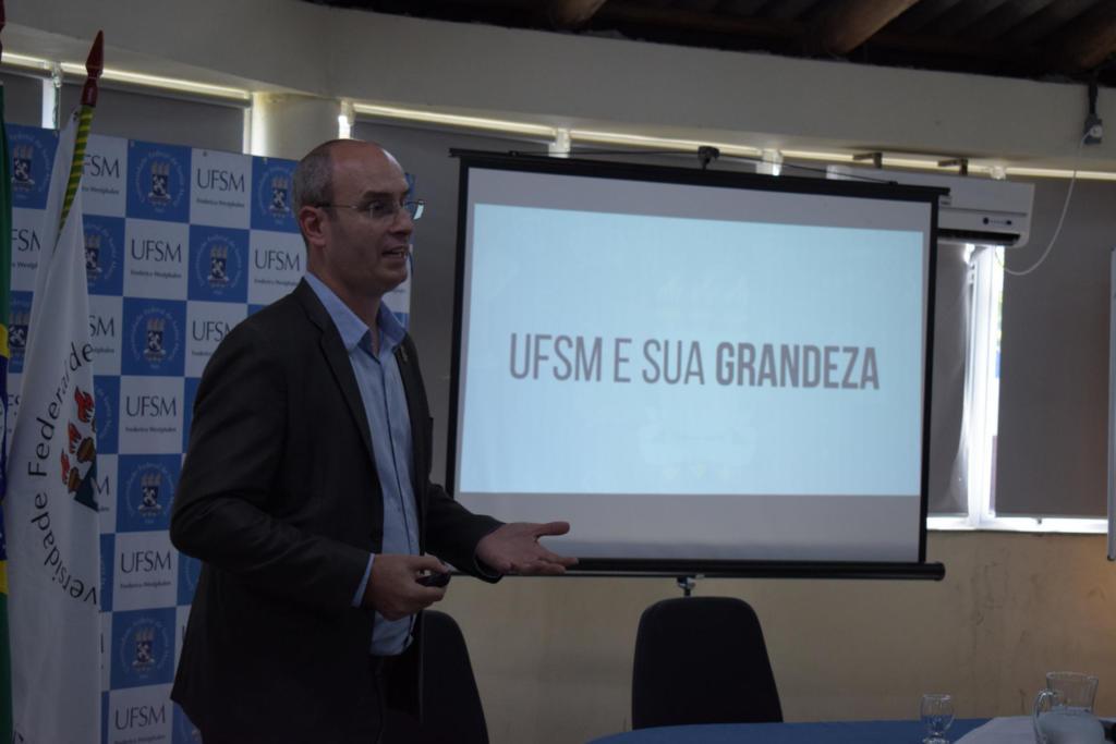 Foto horizontal, em cores, do pró-reitor em pé à frente do público. Ele apresenta um slide sobre a UFSM com a seguinte inscrição: