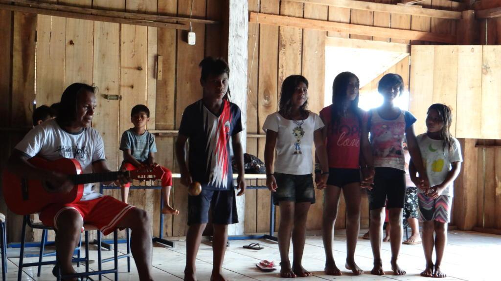 Foto colorida horizontal mostra crianças indígenas cantando enquanto um indígena adulto toca violão