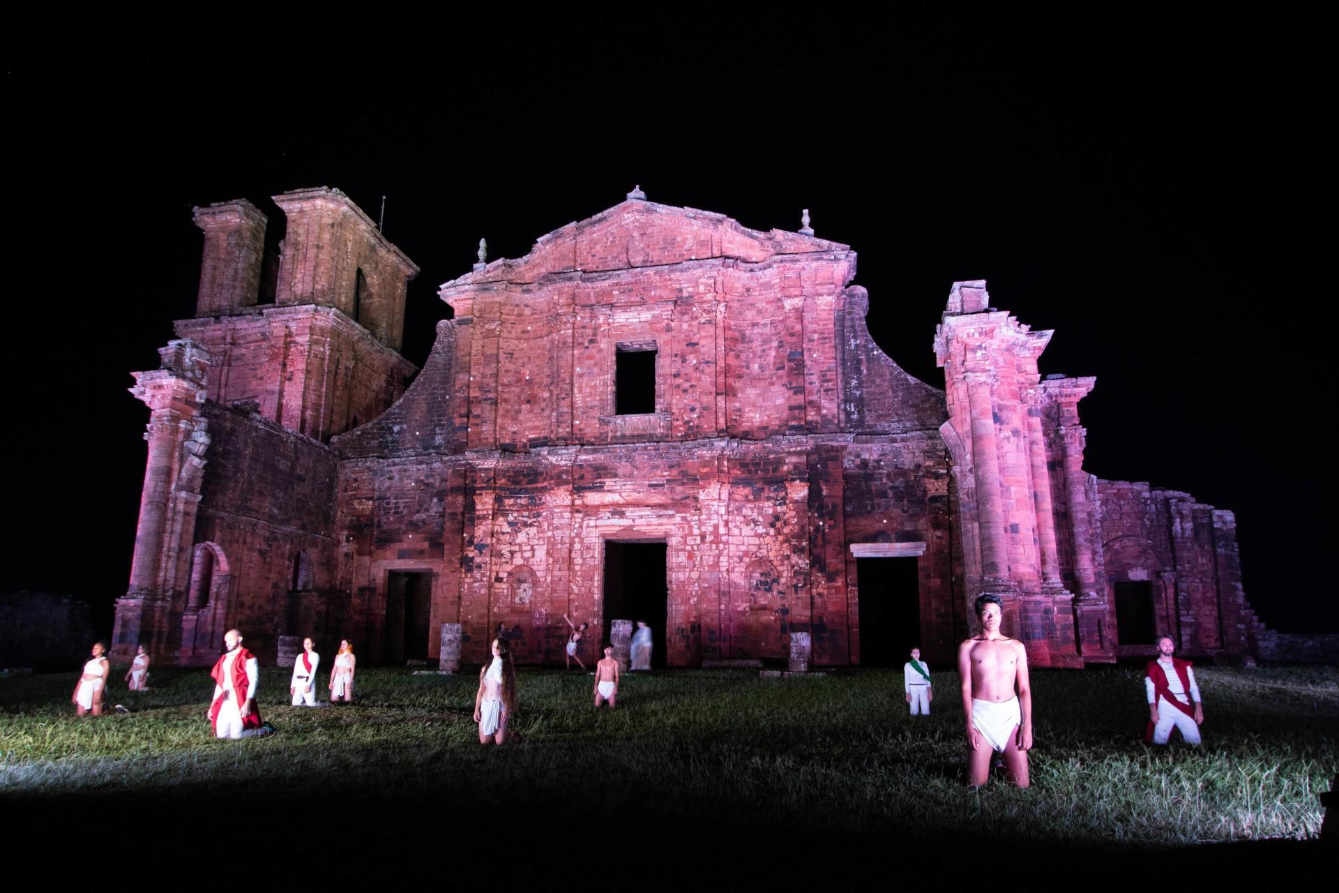 Foto colorida horizontal mostra cena do espetáculo, com os dançarinos em ação em frente às ruínas iluminadas de rosa à noite