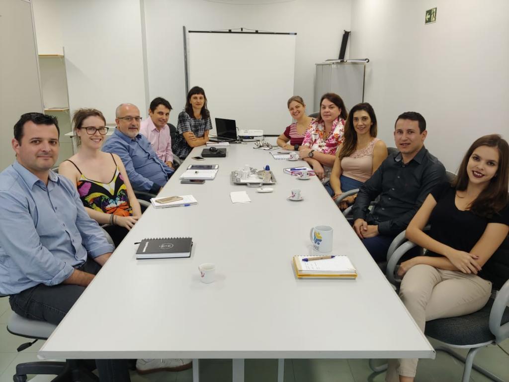 Foto horizontal a cores com os membros da comissão sentados ao redor de uma mesa e olhando para a câmera