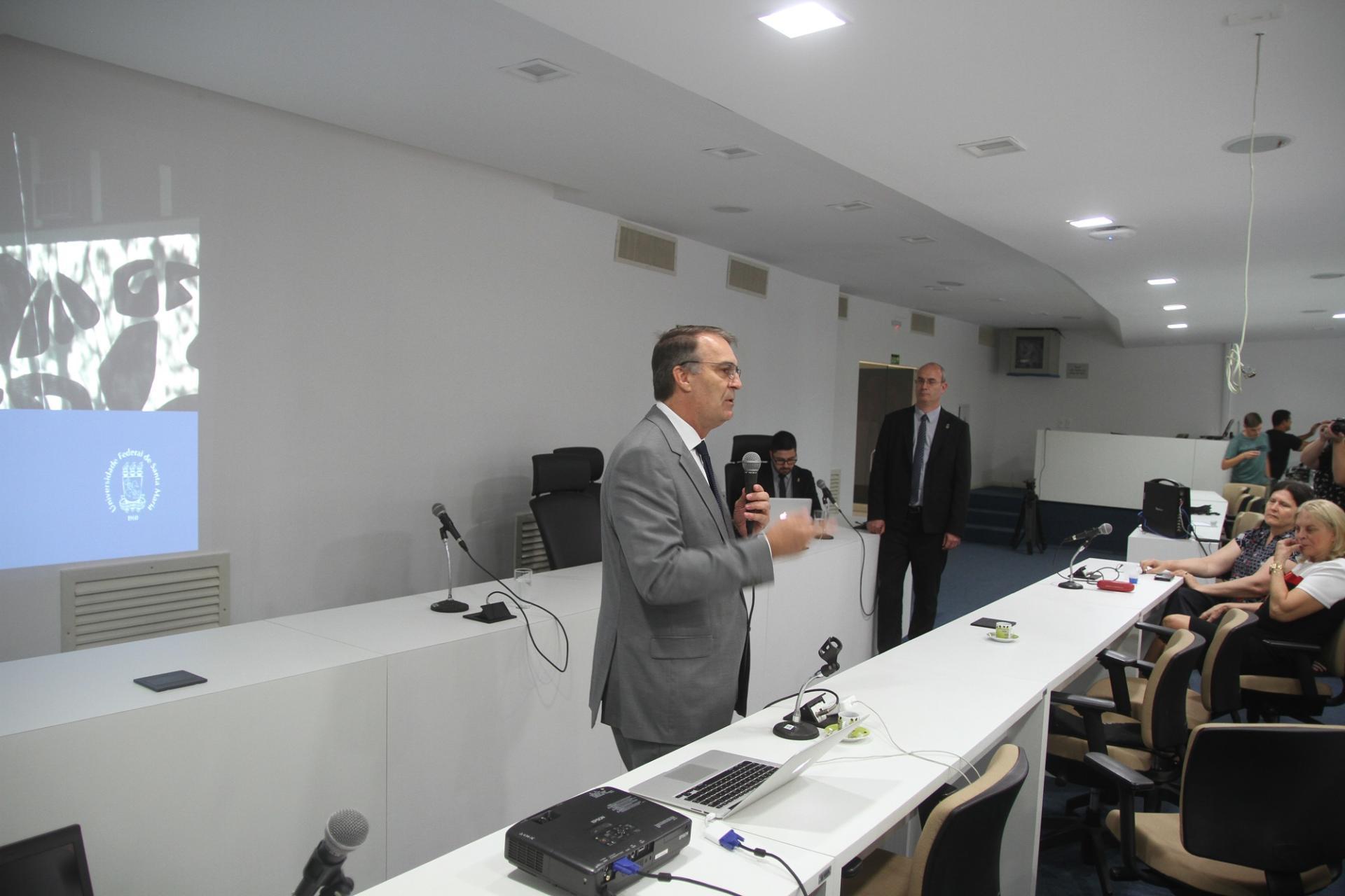 Foto colorida horizontal mostra reitor e vice em primeiro plano, ambos em pé, na Sala dos Conselhos, enquanto o reitor fala ao público