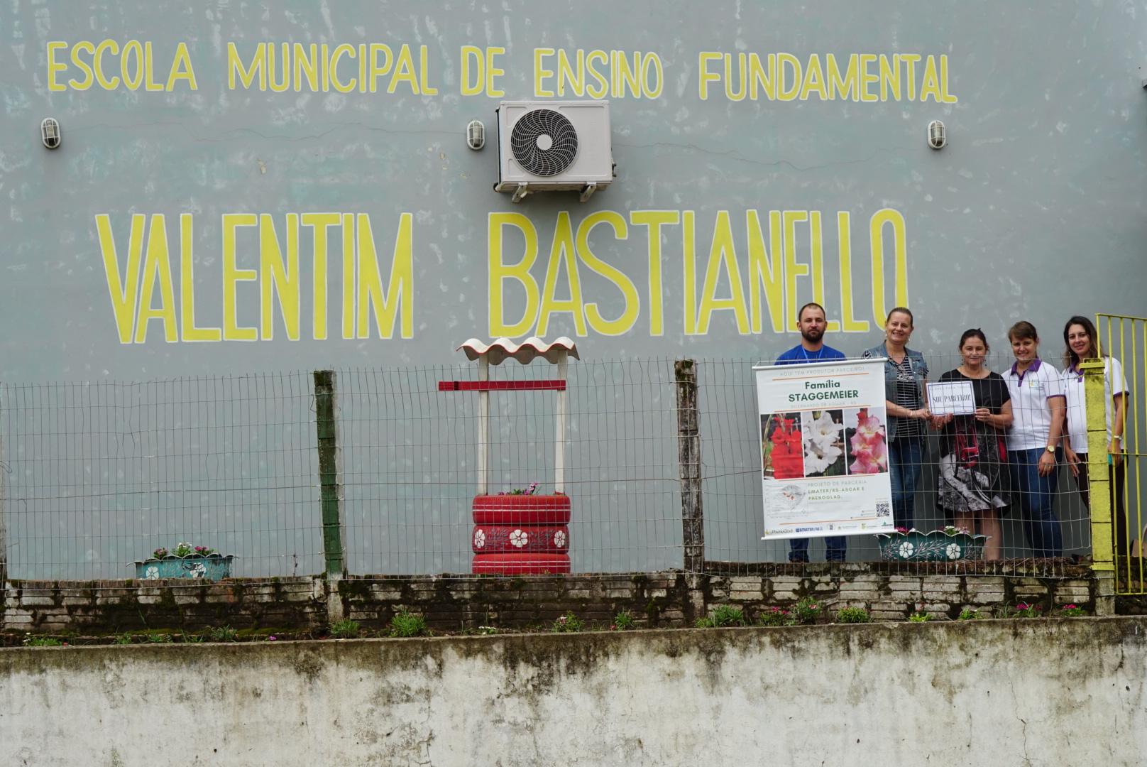 Foto colorida horizontal mostra pessoas em frente a uma parede onde aparece o nome da escola escrito em amarelo