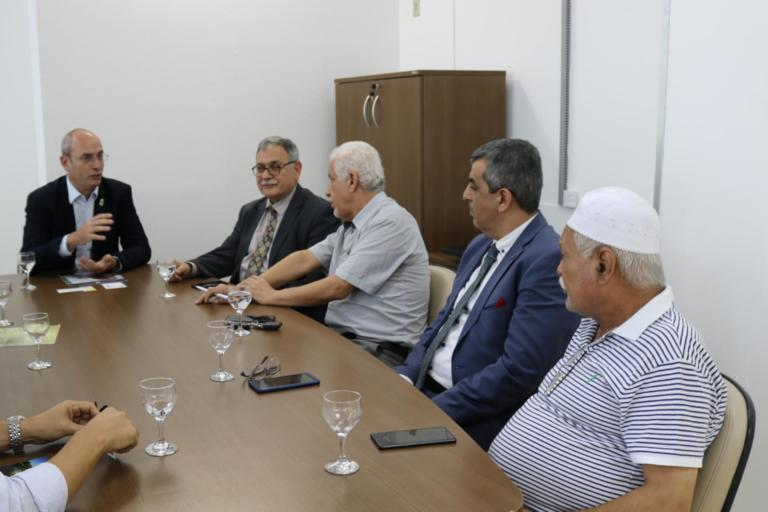 Foto horizontal de cinco homens sentados à mesa, no gabinete do reitor. Na ponta da mesa está o vice-reitor e do lado direito da imagem está a comitiva com quatro homens