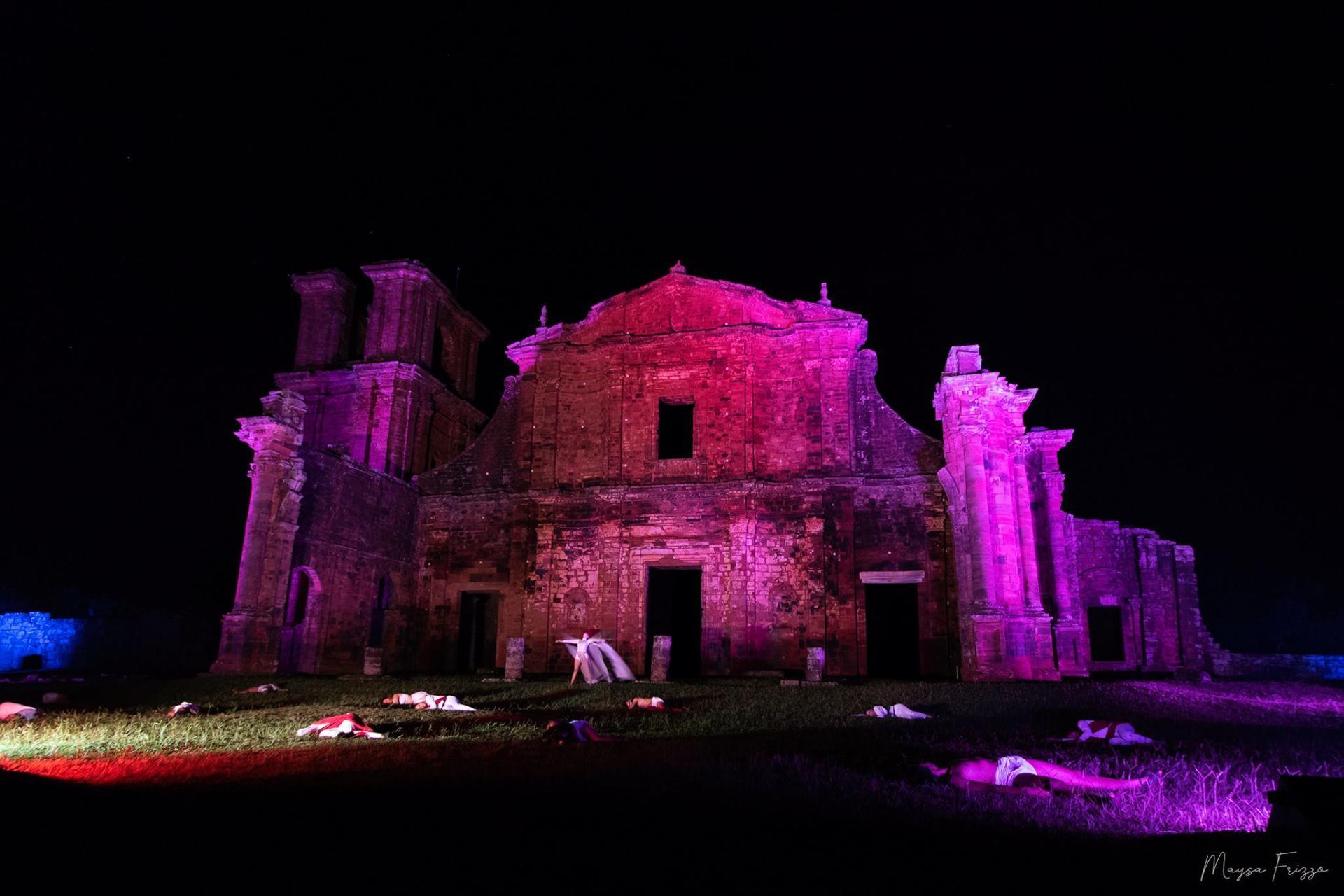 Foto mostra as ruínas de São Miguel à noite, iluminada de roda, com bailarinos à frente apresentando o espetáculo, a maioria deles deitados no chão