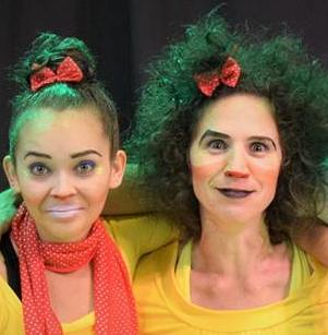 """Foto colorida das duas artistas caracterizadas como """"as irmãs pulgas"""", com rosto pintado, roupa amarela e laços vermelhos nos cabelos"""