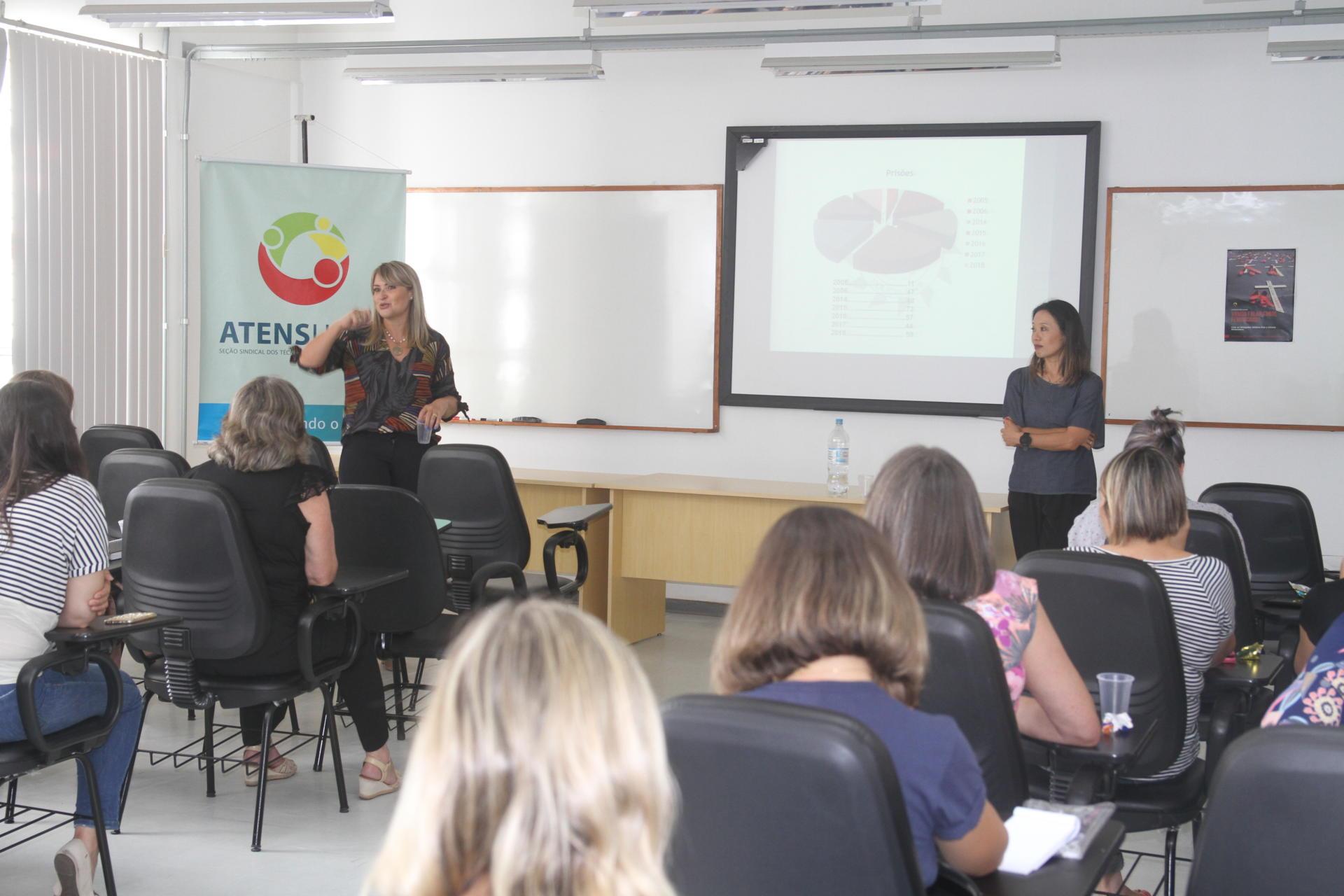 Foto colorida horizontal com duas mulheres à frente de um público formado por mulheres em um pequeno auditório. Ao fundo, banner da Atens