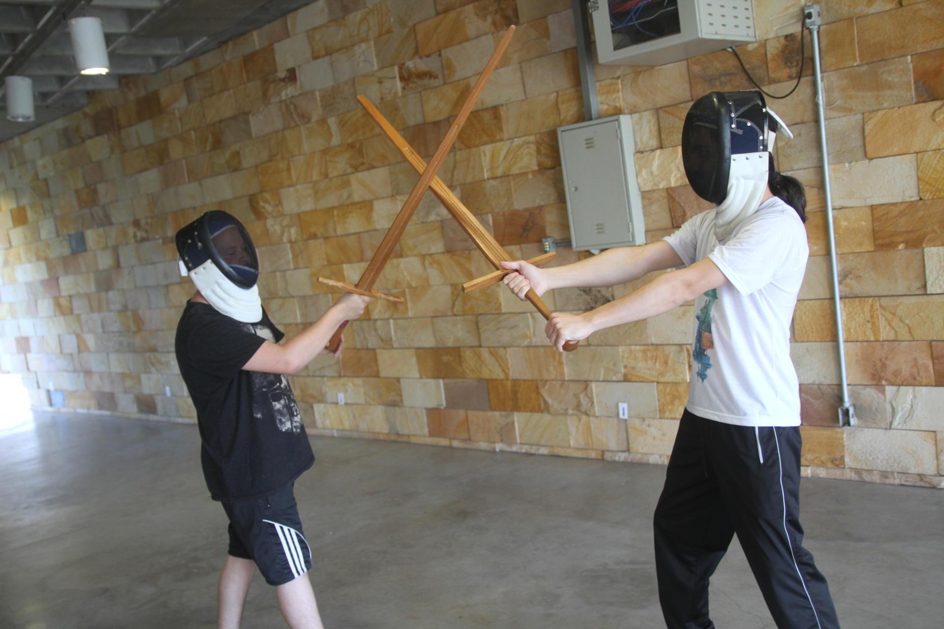 Foto colorida horizontal mostra duas pessoas, com máscaras e espadas de madeira, simulando uma luta
